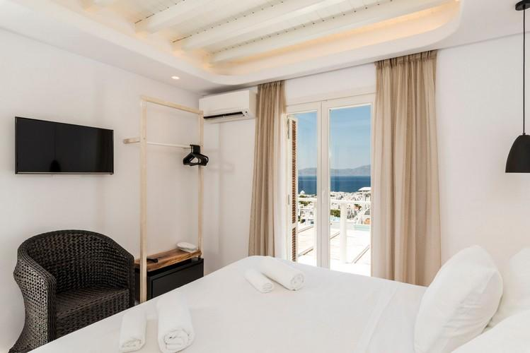 bedroom with air condition flat screen tv and black chair