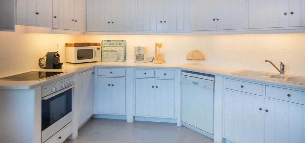simply designed kitchen with white cabins and lamps