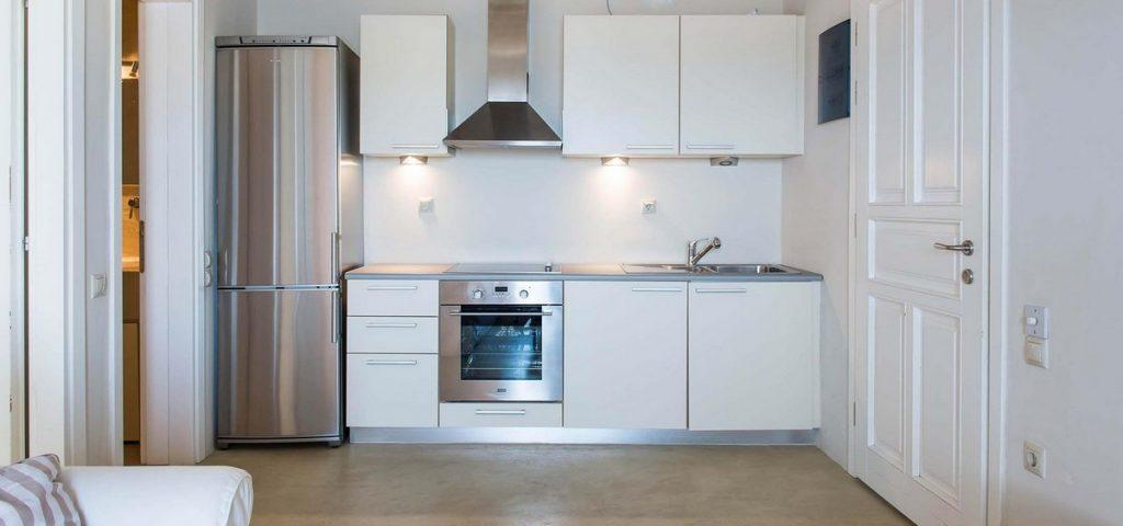 fully equipped kitchen with stainless steel oven and fridge