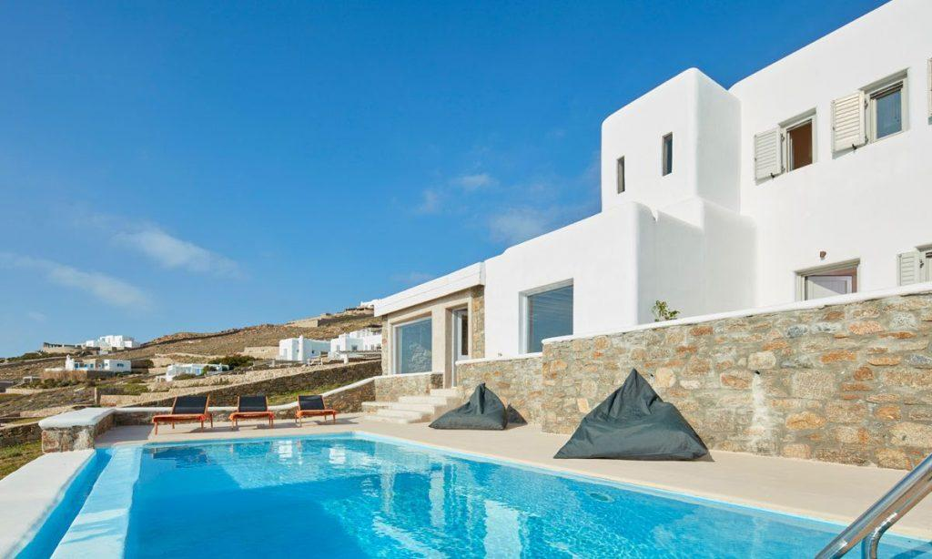 Villa Orion Retreat, Houlakia, Mykonos, villa exterior, sun beds, pool, climbers, sky, clouds