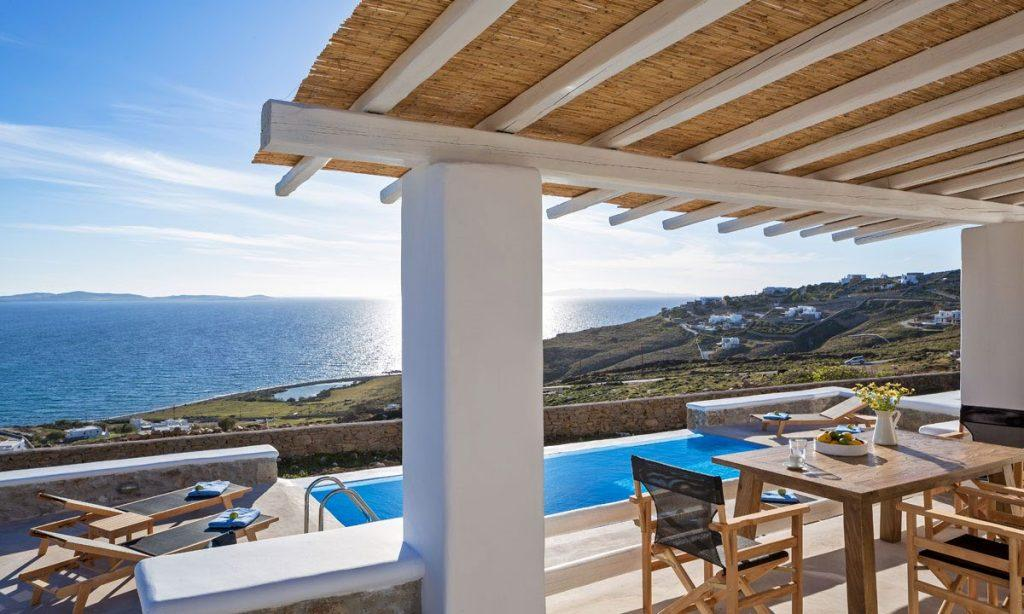 Villa Orion Retreat, Houlakia, Mykonos, outdoor, table, chairs, flowers, vase, glass, pool, climbers, towels, sky, sea