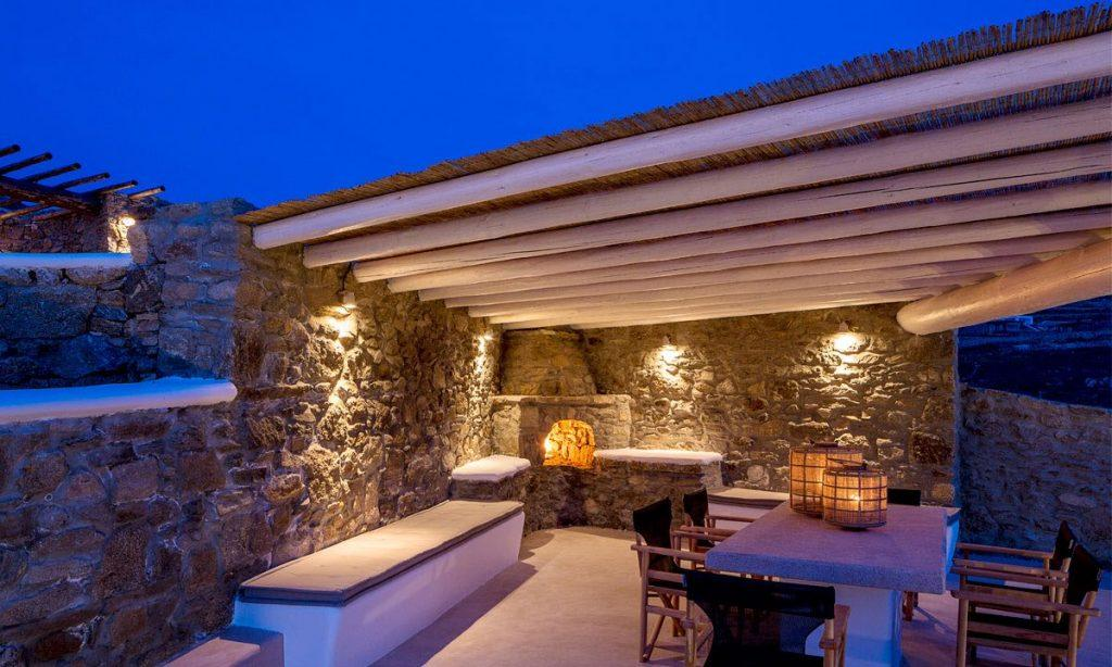 Villa Orion Retreat, Houlakia, Mykonos, outdoor, dining area, dining table, chairs, lamps, night, lights
