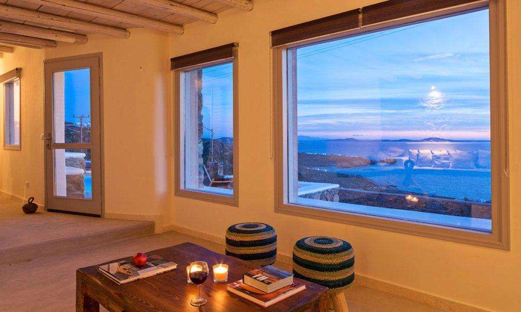 Villa Orion Retreat, Houlakia, Mykonos, living room, table, glass, wine, books, candles, chairs, window, view, sea, sky