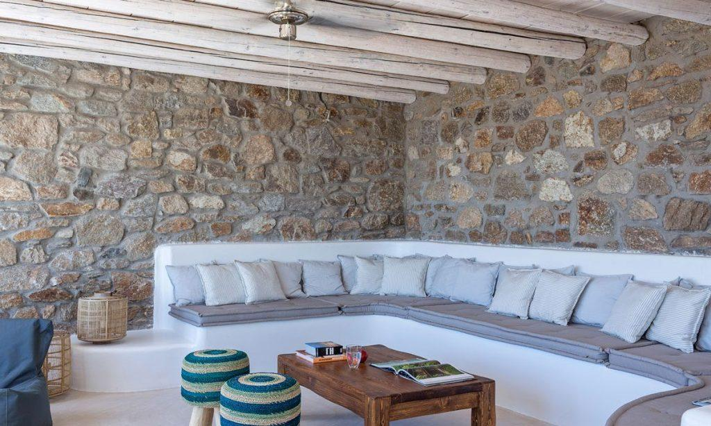 Villa Orion Retreat, Houlakia, Mykonos, outdoor, resting area, pillows, sofa, stone wall, table, books, glass, chairs