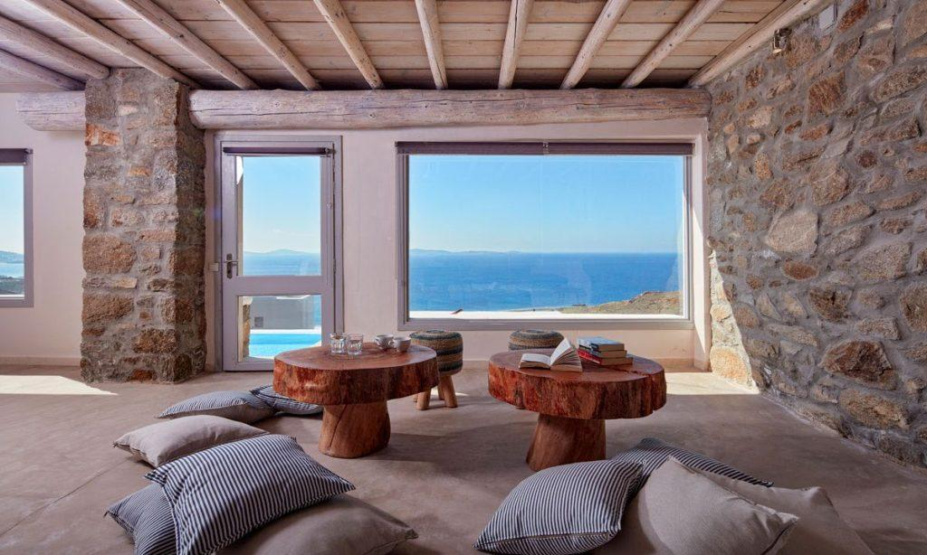 Villa Orion Retreat, Houlakia, Mykonos, interior, living room, pillows, carpet, tables, books, glasses, cups