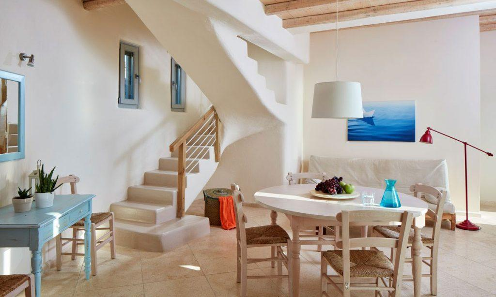 Villa Orion Retreat, Houlakia, Mykonos, living room, table, chairs, sofa, pillows, painting, desk, mirror, stairs, basket, lamp