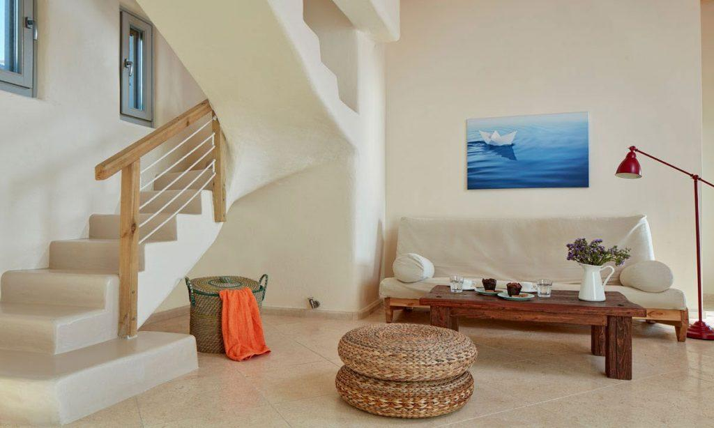 Villa Orion Retreat, Houlakia, Mykonos, living room, sofa, pillows, painting, stairs, basket, table, cookies, plates, glasses, vase, flowers, lamp