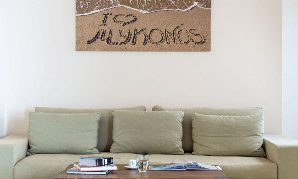 Villa Orion Retreat, Houlakia, Mykonos, painting, sofa, pillows, table, glass, water, cup, coffee, books
