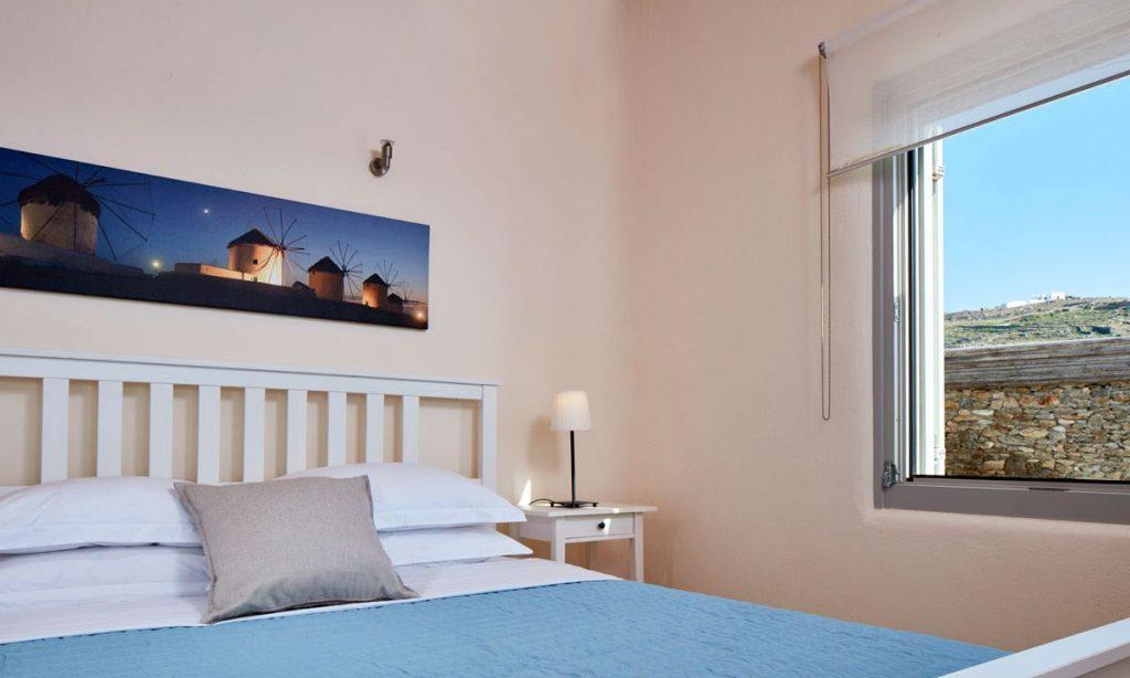 Villa Orion Retreat, Houlakia, Mykonos, bedroom, king size bed, pillows, painting, window, curtain, lamp, nightstand
