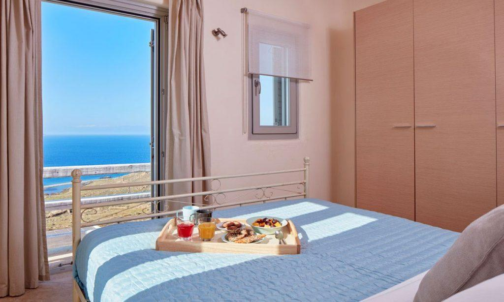 Villa Orion Retreat, Houlakia, Mykonos, bedroom, king size bed, curtains, closet, window, door, food, breakfast in bed, sea, view