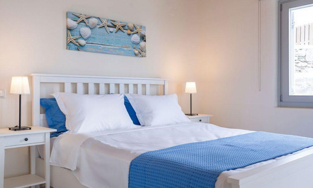 Villa Orion Retreat, Houlakia, Mykonos, bedroom, king size bed, painting, lamps, nightstands, windows, blanket, pillows