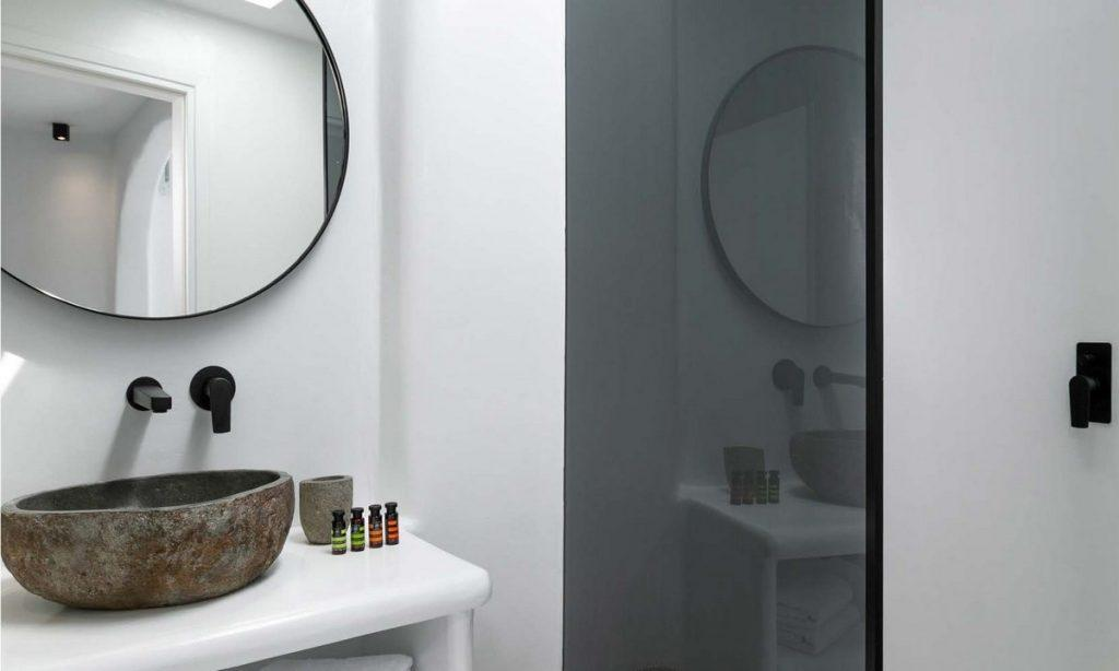 simply designed bathroom with round mirror