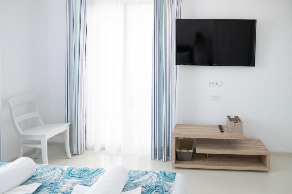bedroom with large window that provides daylight, white walls and large TV ideal for relaxing