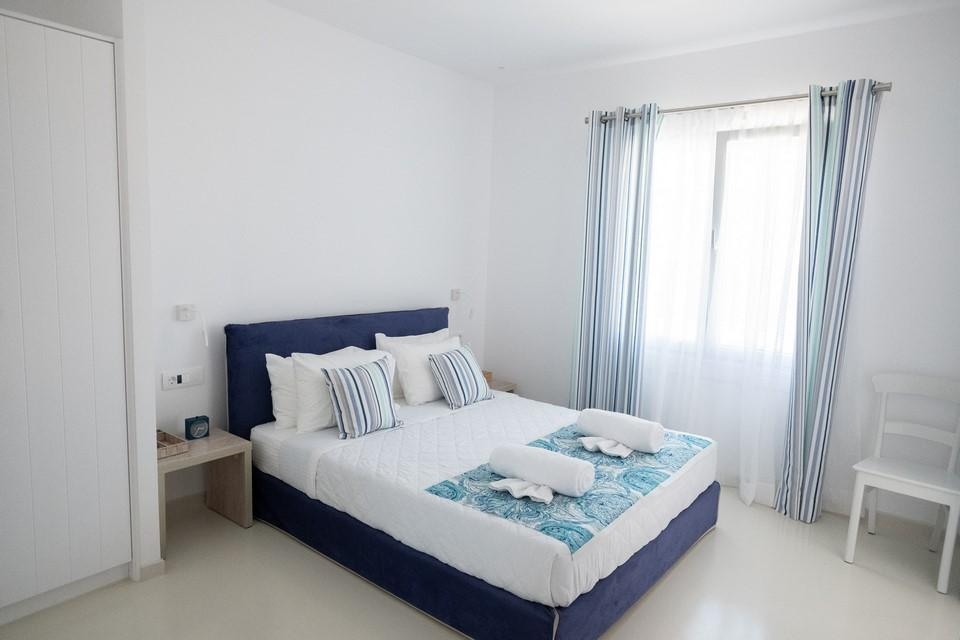 lit by daylight bedroom whit white walls equipped with blue comfortable king size bed and bedside table