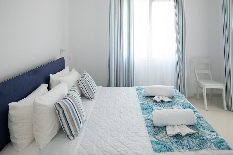 lit by daylight bedroom with white walls and comfortable king size bed