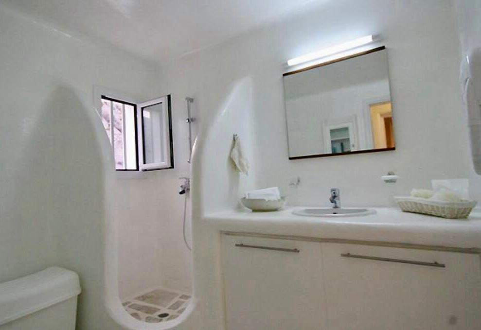 white wall bathroom with lit mirror and small window