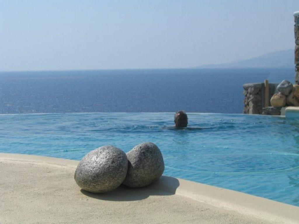 outdoor area with pool and sea horizon view