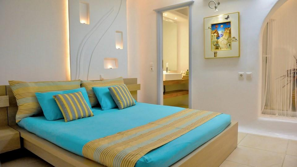 lit bedroom with blue and yellow bed sheets and wall paint
