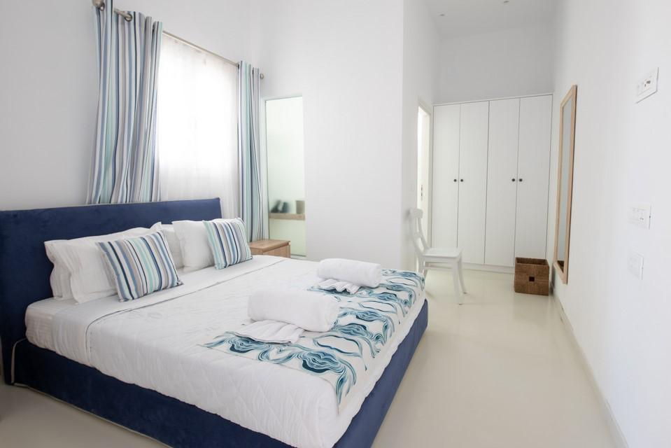 spacious tiled floor bedroom with bed and white huge cabin