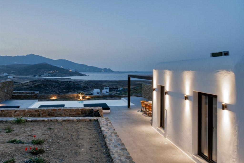 outdoor area with lit villa walls and beautiful landscape