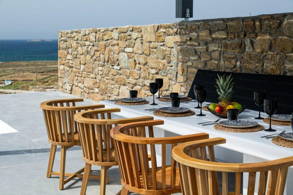 outdoor dinning area with wooden chairs and white ceramic table