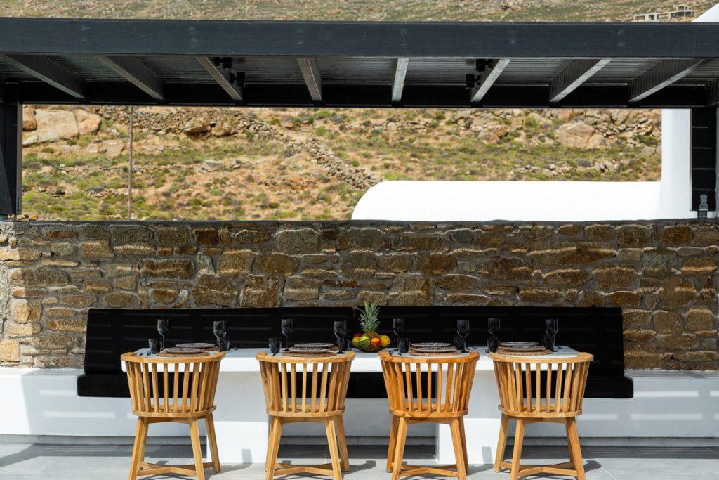 outdoor area with wooden chairs and black glasses