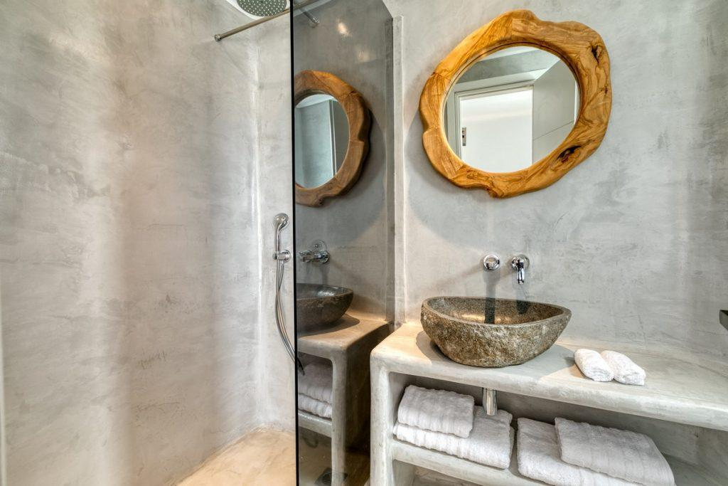 grey bathroom walls with wooden mirror frame and sink