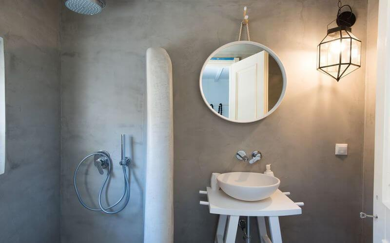 simply designed bathroom with round mirror and shower