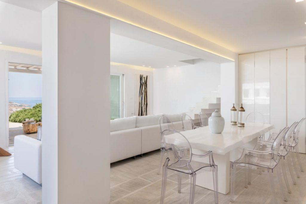 white designed living area with ceramic huge table and transparent chairs