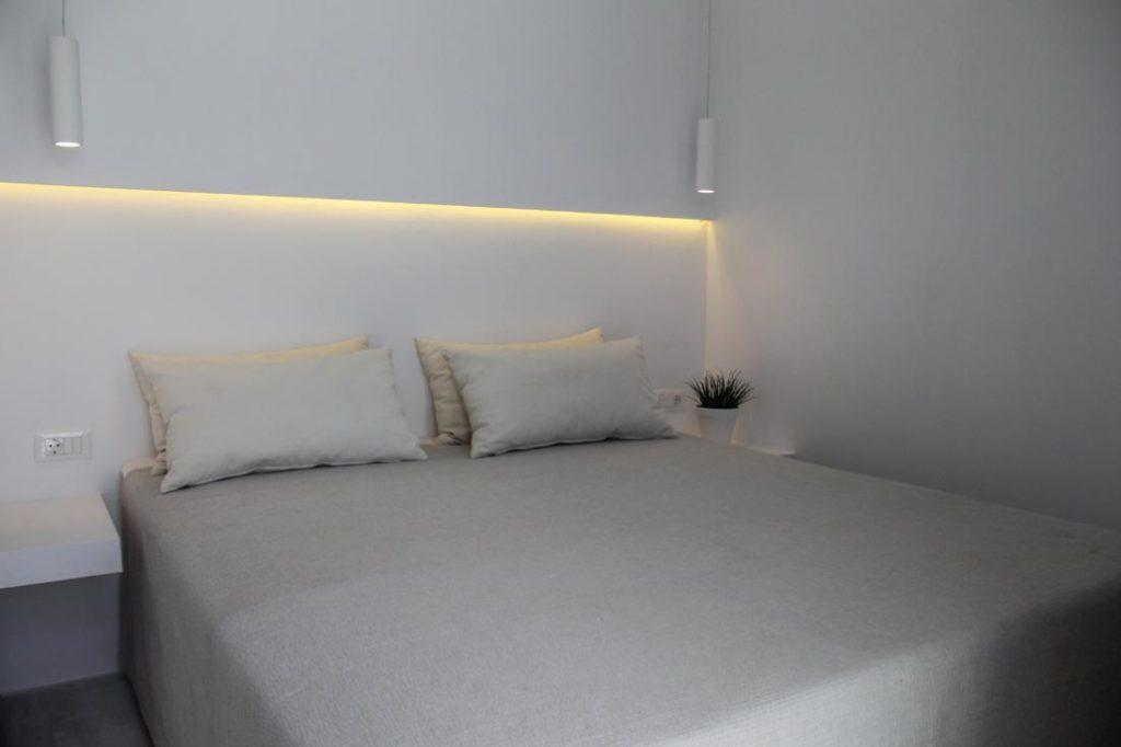 bedroom with lamps above bed and soft pillows