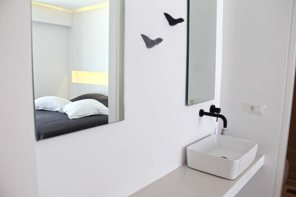 simply designed bathroom with mirrors and washstand