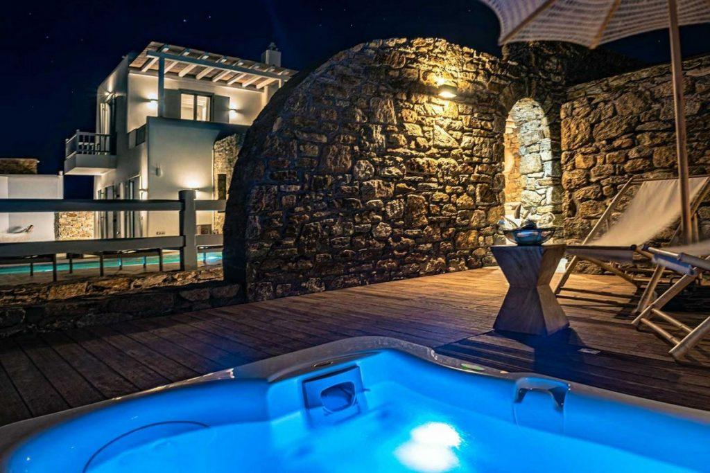 outdoor area with lit jacuzzi and umbrella