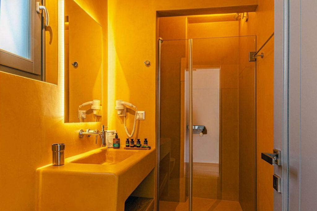lit bathroom with nice shower and huge clean mirror