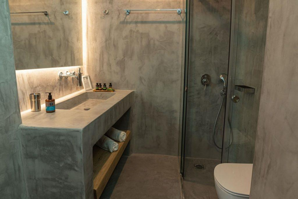 grey wall bathroom with glass shower and towel rack