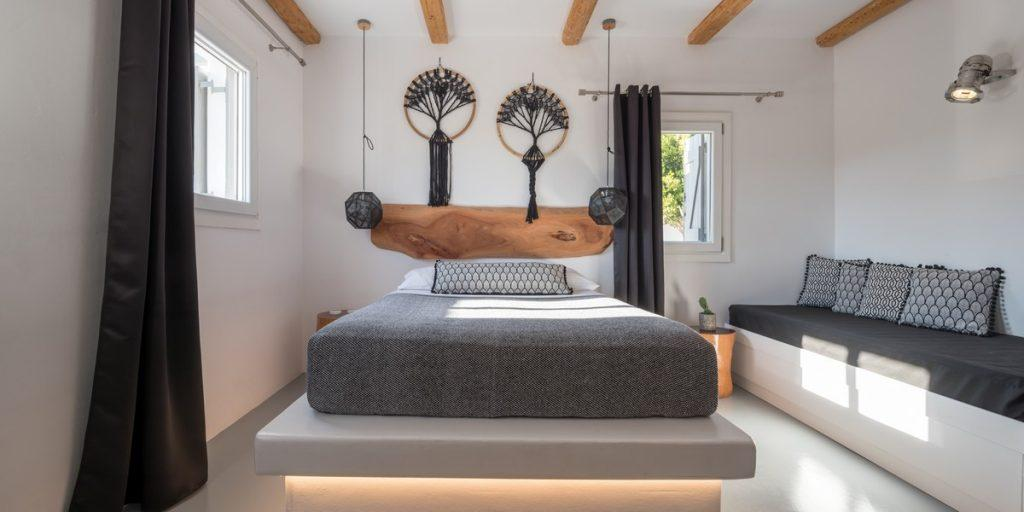 bedroom with wooden frame above bed and wall lamps