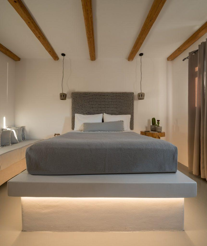 bedroom with lit bed and hanging lamps