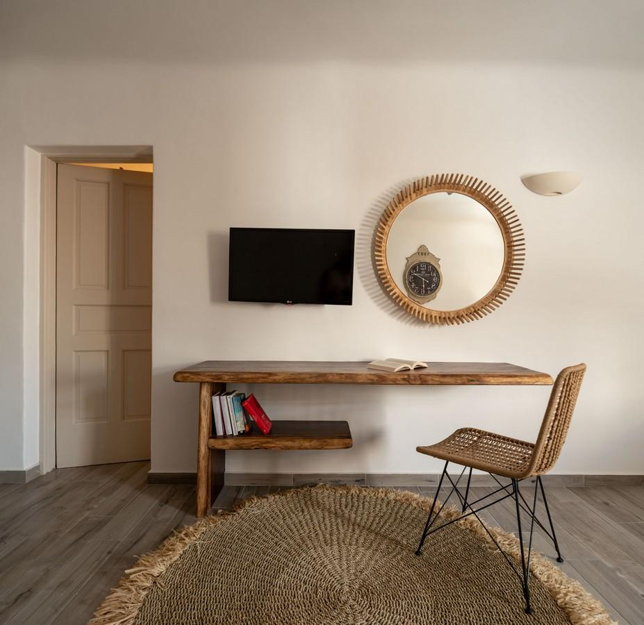 wooden table and knitted chair to read a book or any other activity and wall mount TV and round mirror