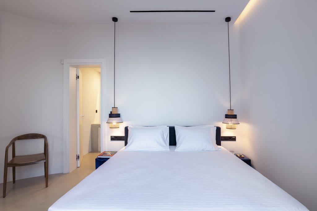 rand bedroom containing king size bed two nightstands and lamps hanging from the ceiling