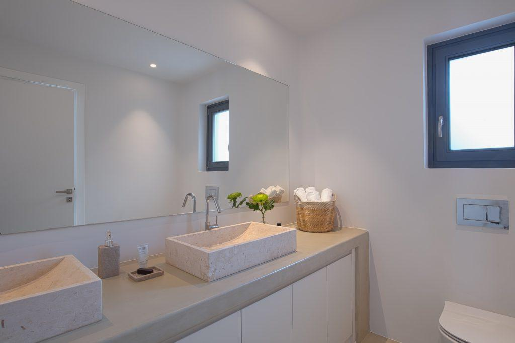 bathroom with huge mirror and unique ceramic sinks to clean up