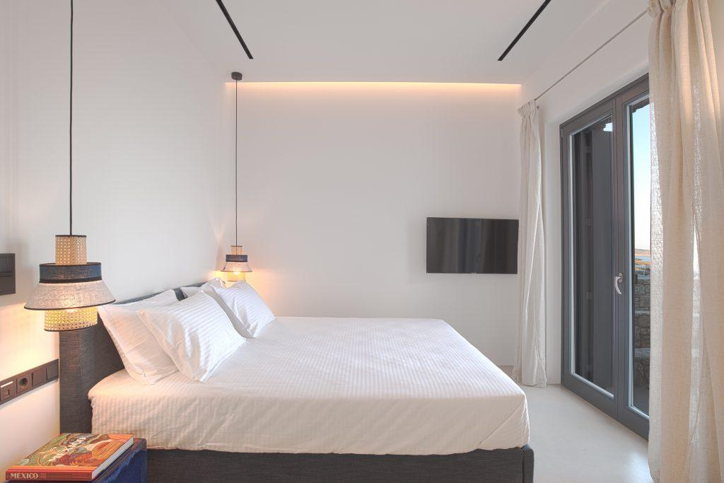 wide double bed facing window walled sea view