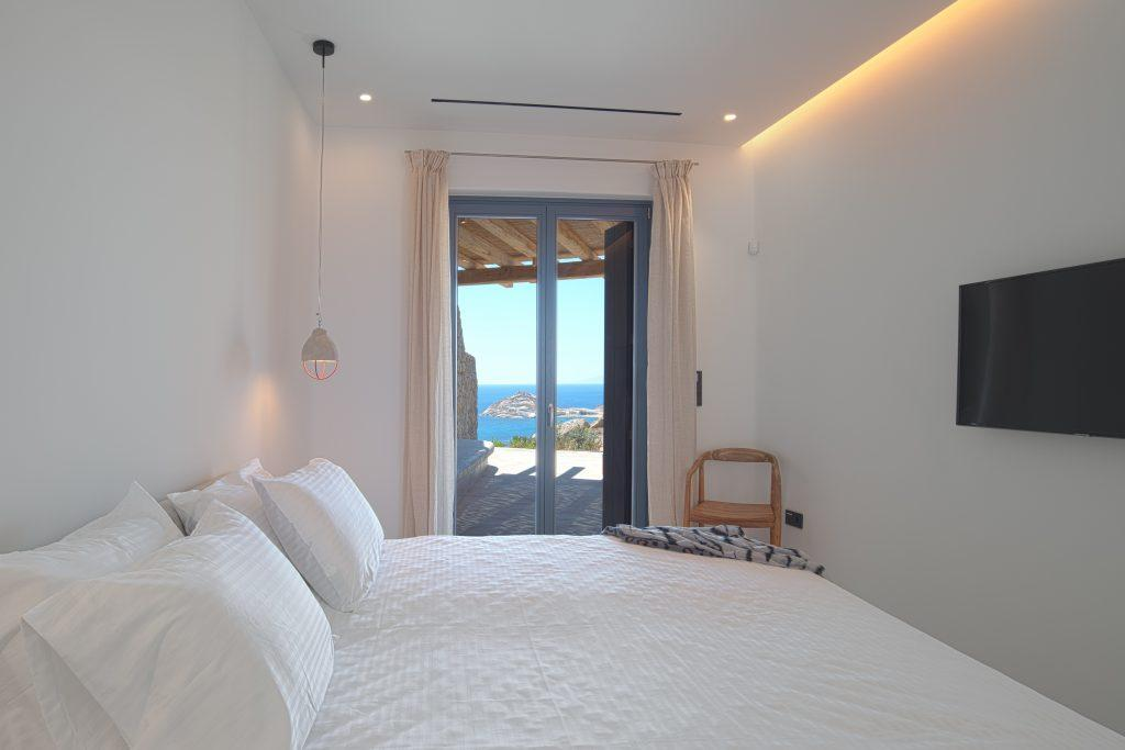 snug bedroom with breathtaking window wall view of the sea and chair n the corner