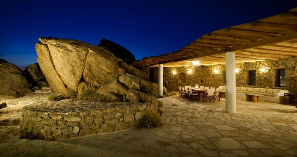 out door dining room with rock walls and big stone decoration