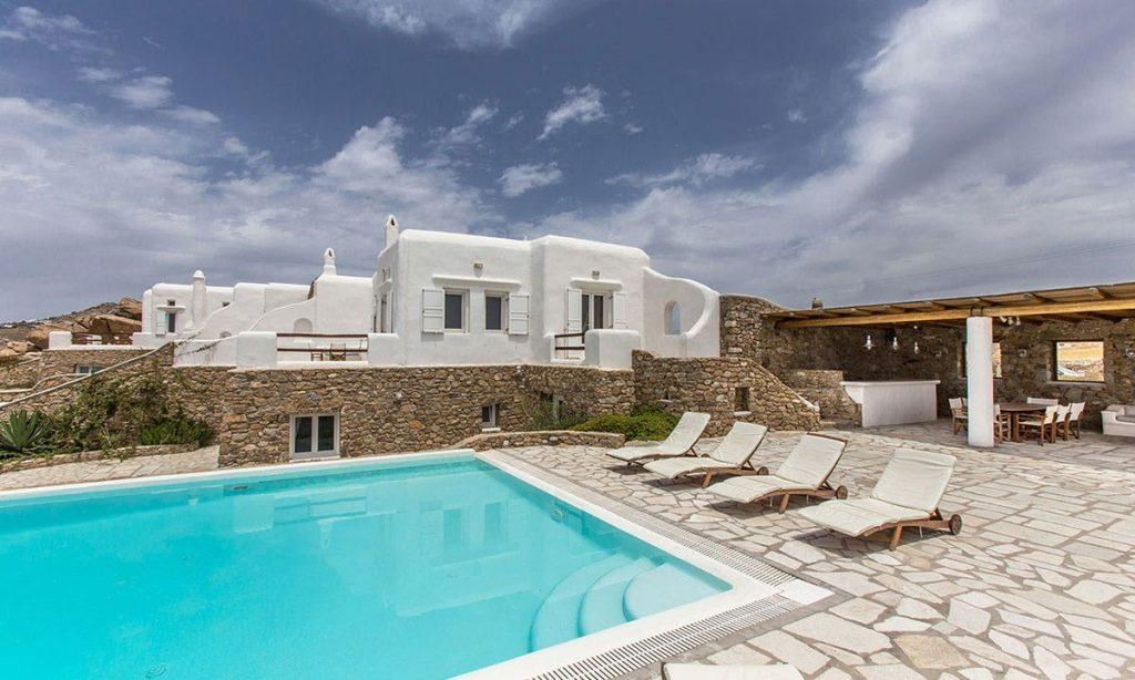 balcony with white walls and stone and swimming pool with sitting area