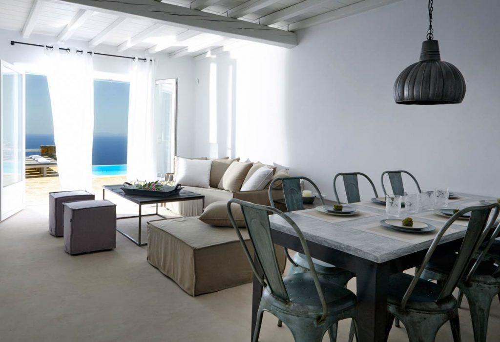 dining room with plates and glasses of water and out door view of sea
