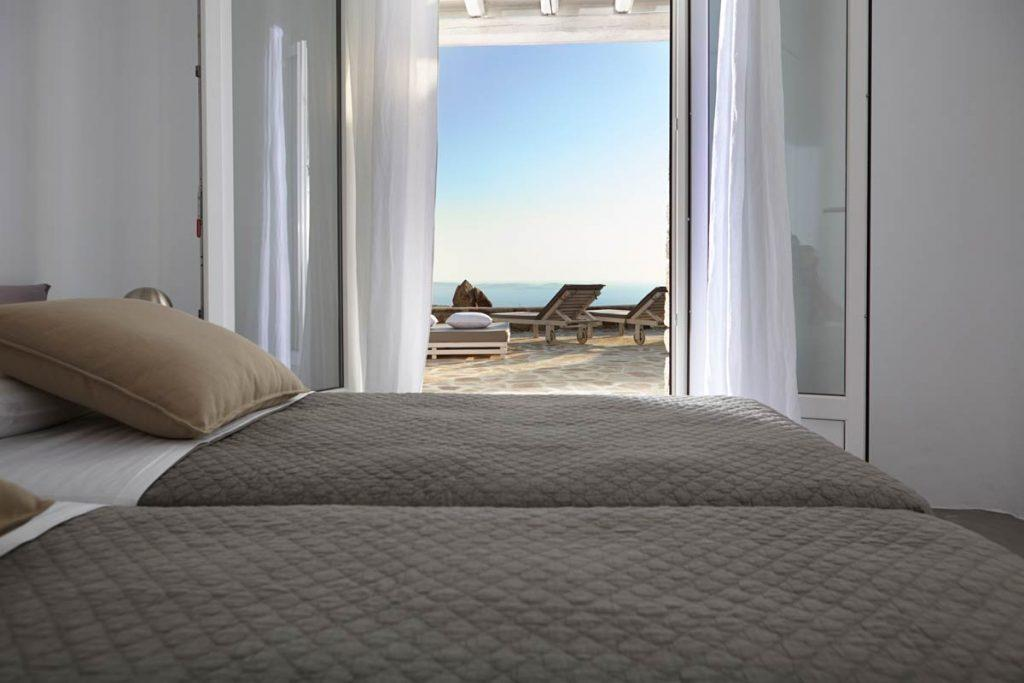 bedroom with beige gray and separated beds and view of sea