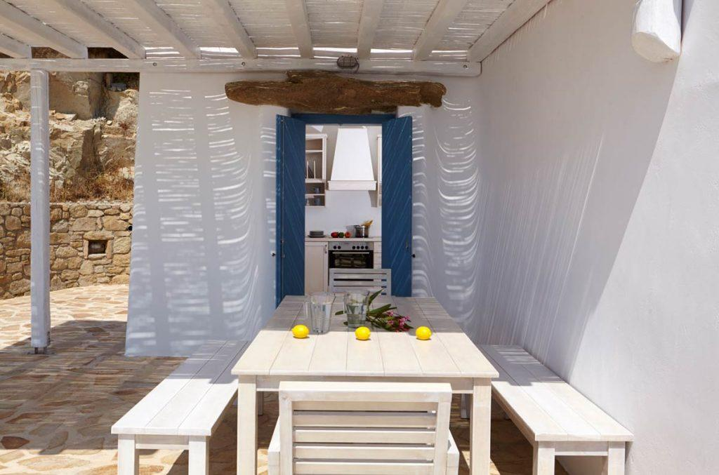 white wall dining out door area with glasses of water and lemons overlooking the kitchen