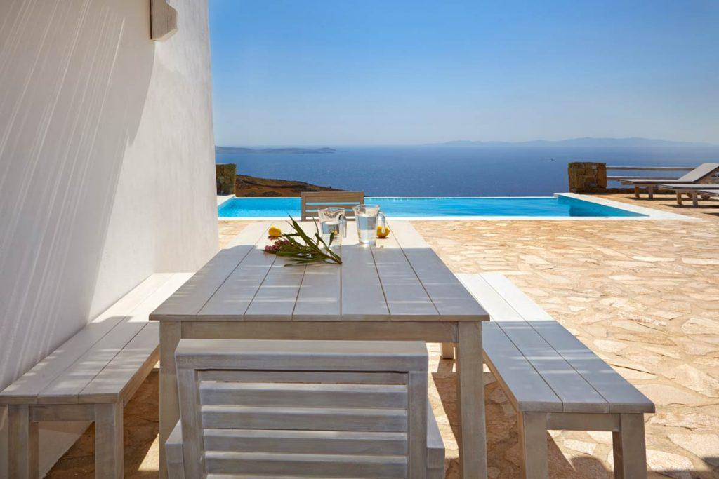 wood table with benches overlooking the pool and the beautiful sea