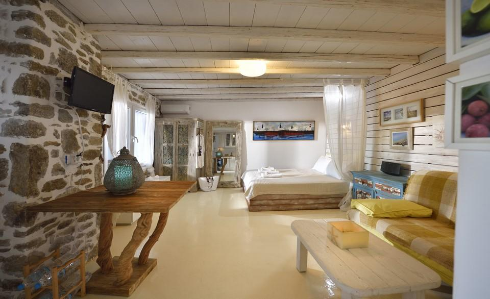 spacious bedroom with a combination of white wooden and stone walls with king size bed ideal for resting