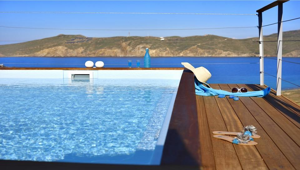 view of the crystal blue sea and nature from the pool of cooling water surrounded by a wooden counter