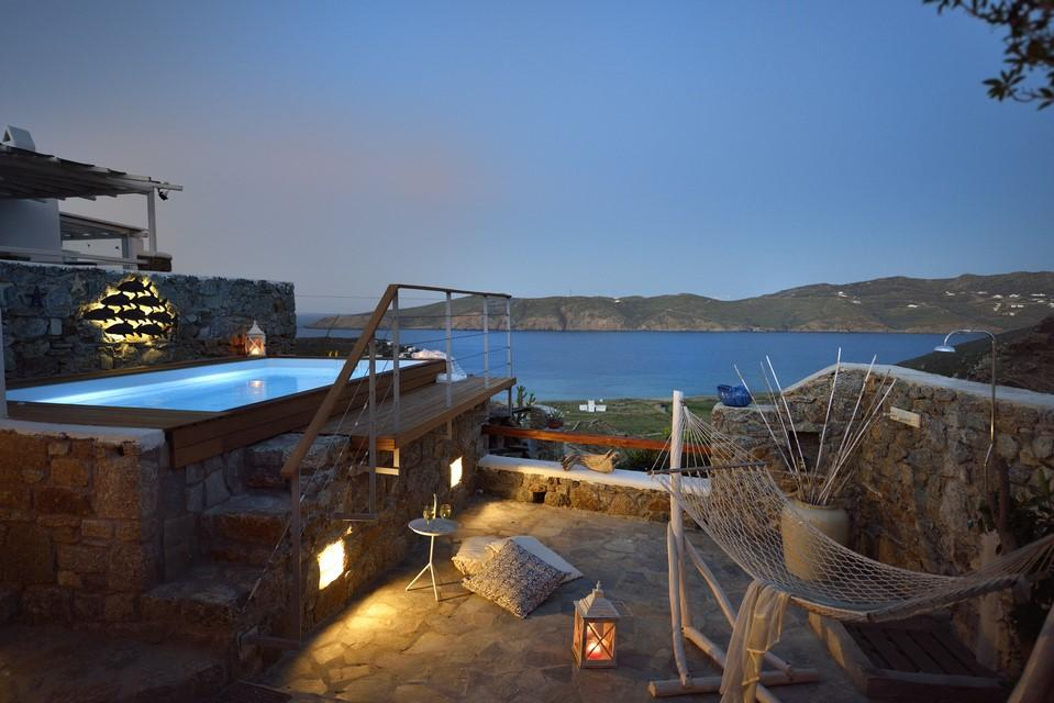 ideal for a romantic evening in a pool made of stone and wood with a special detail of lamps and a wicker swing